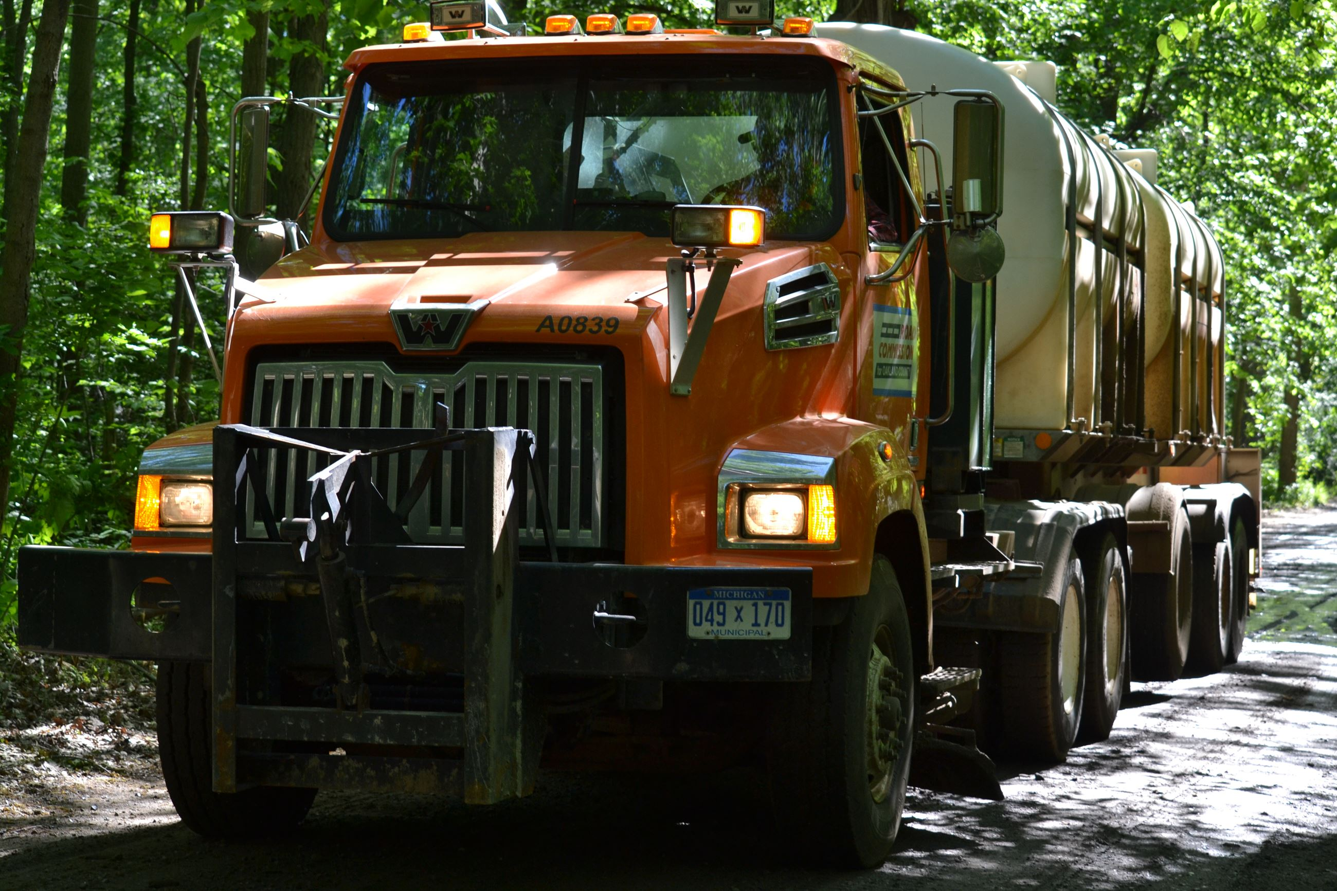 RCOC truck applying brine to a gravel road