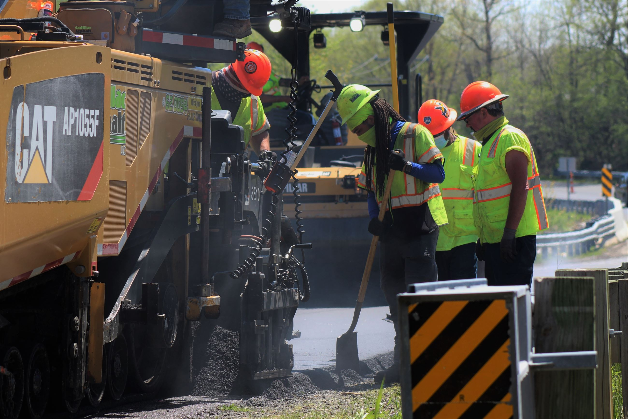 Construction Worker Uses Shovel After Asphalt Has Been Laid